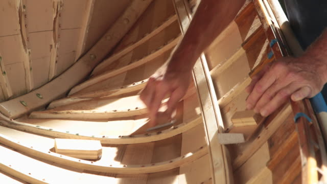 cu mature male hands sanding the inside of a wooden boat - building activity stock videos & royalty-free footage