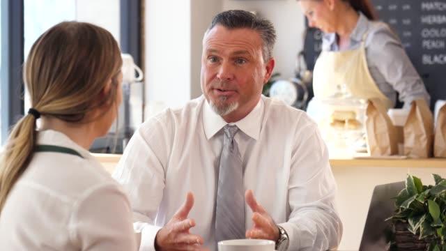 vídeos de stock, filmes e b-roll de um gerenciador de maduro, masculino se senta em uma mesa em sua loja de café e tem uma discussão com um funcionário. - barista