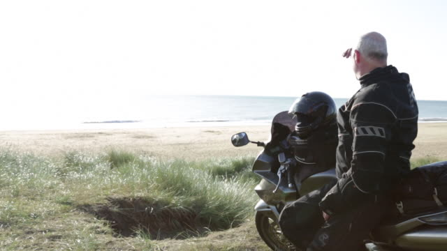 mature male motorcyclist sitting on his touring bike puts hand up to eyes to look out to sea. - only mature men stock videos & royalty-free footage
