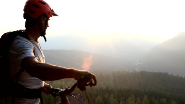 Mature male mountain biker uses guide rope to navigate steep cliff above trailhead