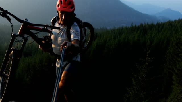 mature male mountain biker uses guide rope to navigate steep cliff above trailhead - mountain bike video stock e b–roll