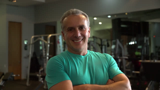mature male personal trainer at the gym facing camera smiling with arms crossed - mature men stock videos & royalty-free footage