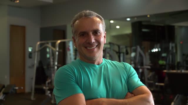 vídeos de stock, filmes e b-roll de treinador de pessoal masculino maduro no ginásio enfrentando câmera sorrindo com braços cruzados - homens maduros