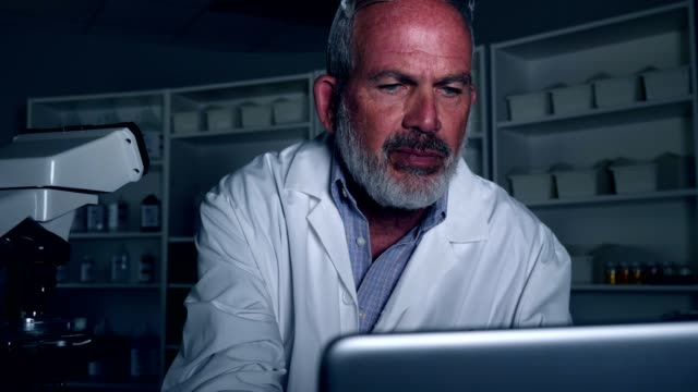 mature male scientist works in a lab at night - concentration video stock e b–roll