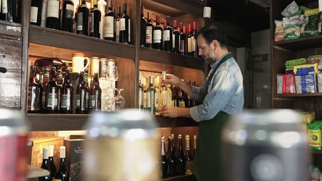 vídeos de stock, filmes e b-roll de proprietário de loja masculina madura reabastecendo prateleira com vinho branco - refresco