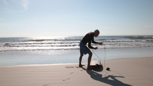 mature male surfer attaching leash to ankle - old diving suit stock videos and b-roll footage