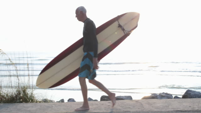 TS Mature male surfer carrying surfboard walking by the sea