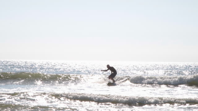 mature male surfer catching a wave - old diving suit stock videos and b-roll footage