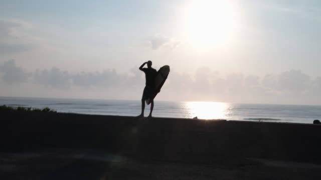 mature male surfer looking out to sea, silhouette - old diving suit stock videos and b-roll footage