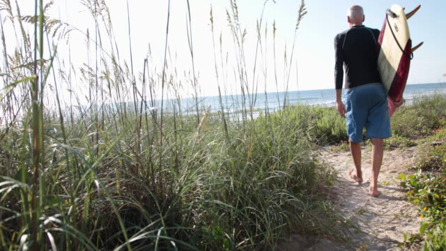 mature male surfer walking along sandy path to the beach carrying surfboard - old diving suit stock videos and b-roll footage