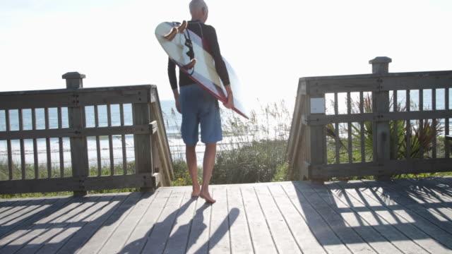 Mature male surfer walking on boardwalk carrying surfboard