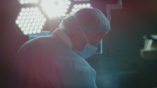 mature male surgeon performing surgery on patient - casualty stock videos & royalty-free footage