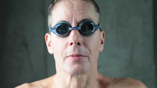 Mature male swimmer lifts head to camera, takes off goggles