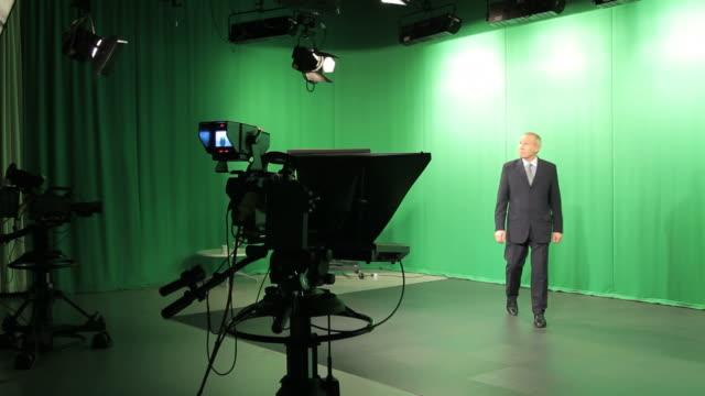 Ältere männliche TV-Moderator zu Fuß von studio