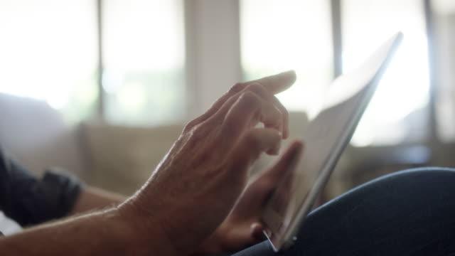 vídeos y material grabado en eventos de stock de hombre maduro usando tableta digital en casa - menos de diez segundos