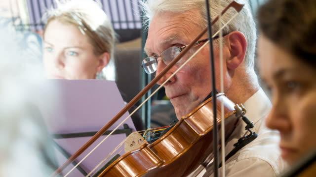 vidéos et rushes de mature male violinist in orchestra - musicien