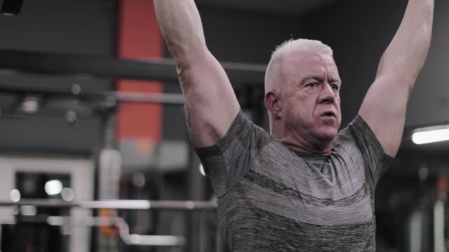 vídeos de stock, filmes e b-roll de mature male weightlifter at the gym - peso livre equipamento para exercícios