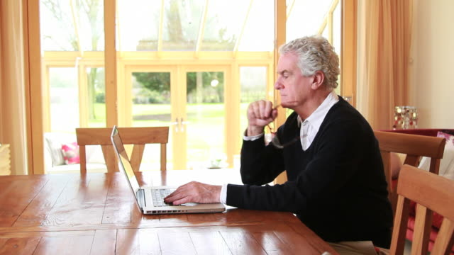 Mature male working on laptop at home