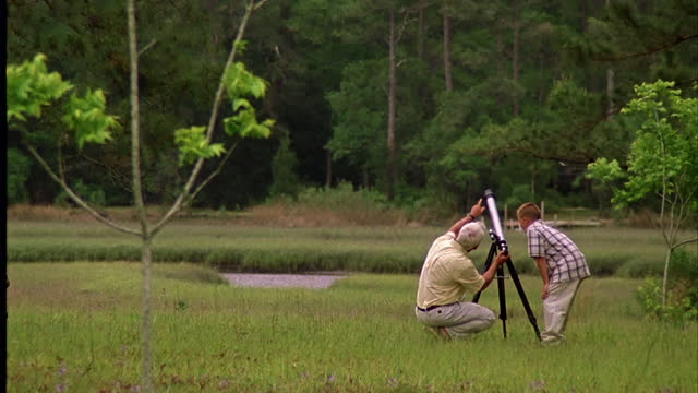 a mature man and a boy look through a telescope in a lush field. - astronomie stock-videos und b-roll-filmmaterial