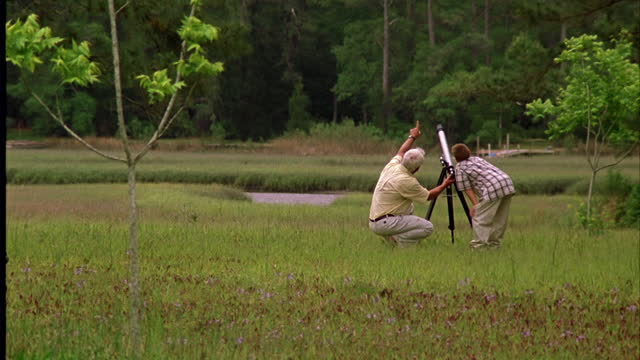 A mature man and a boy look through a telescope in a lush field.