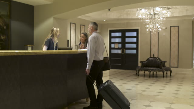 Mature man and a mature woman checking out and leaving a hotel