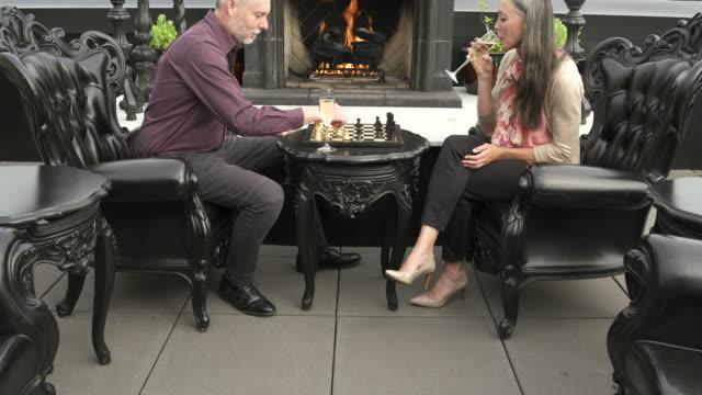 Mature man and a mature woman playing chess