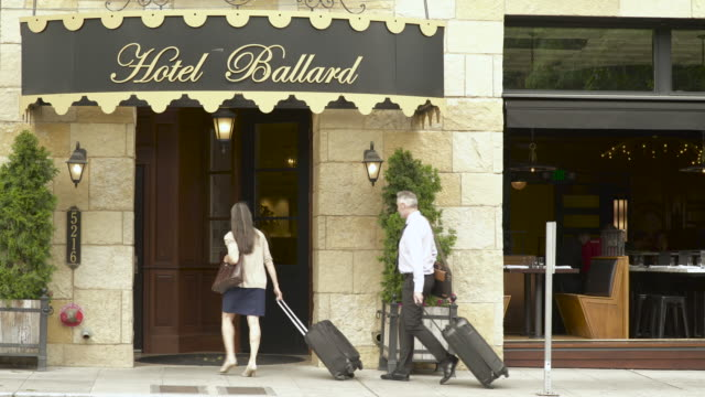 mature man and a woman entering a hotel with their suitcases - wheeled luggage stock videos and b-roll footage