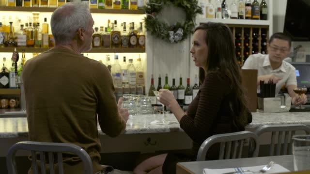 vídeos y material grabado en eventos de stock de mature man and a woman talking and toasting in a bar - cabello canoso