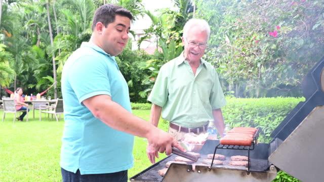 reifer mann und schwiegervater plaudern über barbecue - nur männer stock-videos und b-roll-filmmaterial