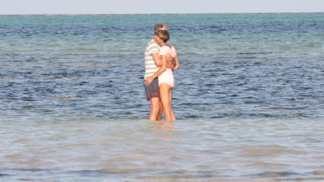 Mature Man and Mid Adult Woman Couple Enjoying in Sea Together