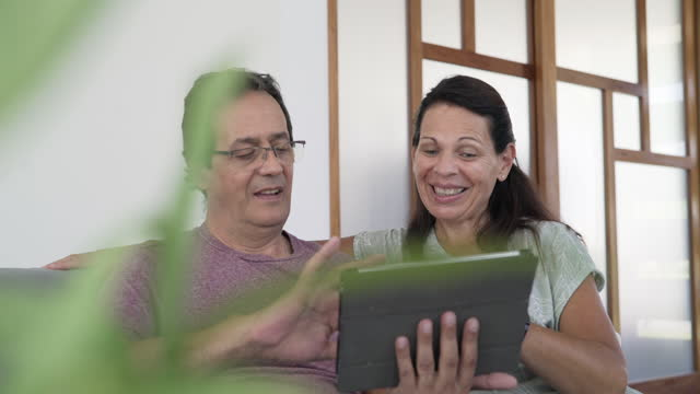 mature man and woman scrolling on digital tablet - portable information device stock videos & royalty-free footage