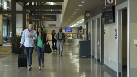 vídeos de stock, filmes e b-roll de mature man and woman walking at an airport arm in arm - mala de rodinhas