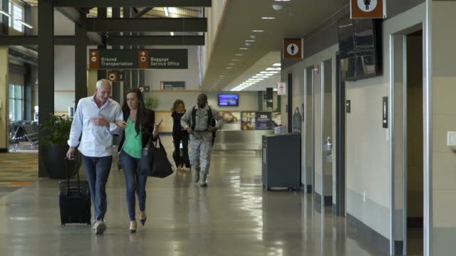 vídeos de stock, filmes e b-roll de mature man and woman walking at an airport arm in arm - de braços dados