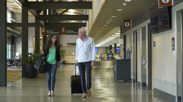 vídeos de stock, filmes e b-roll de mature man and woman walking at an airport with luggage - mala de rodinhas