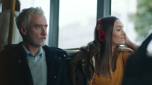 mature man and women with headphones riding on the bus - cable car stock videos & royalty-free footage