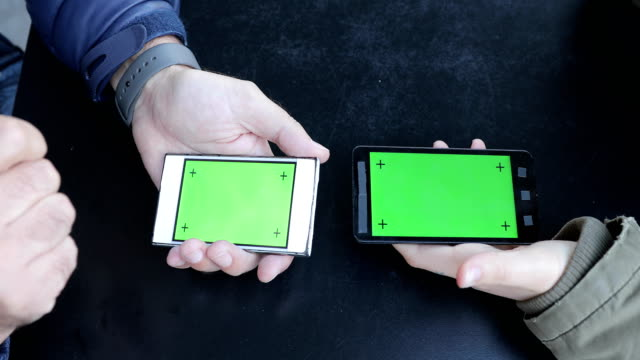 Mature Man and Young Adult Woman Sharing Data on Mobile Phone With Greenscreen