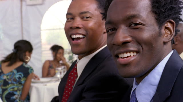 mature man and young man smiling at camera at wedding reception inside tent / arizona - guest stock videos & royalty-free footage