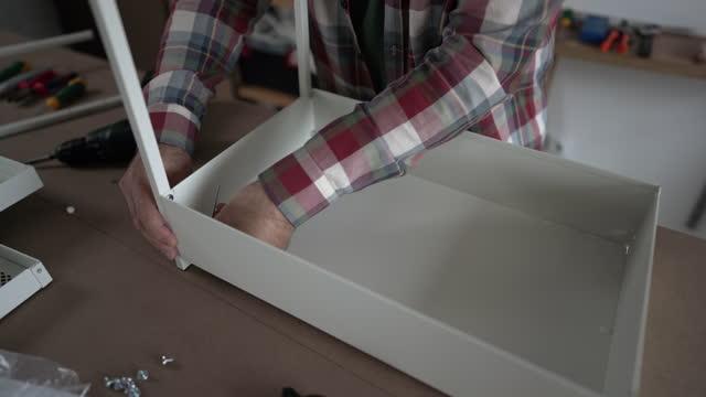 彼の家のワークショップでフラットパック家具を組み立てる成熟した男 - タータンチェック点の映像素材/bロール