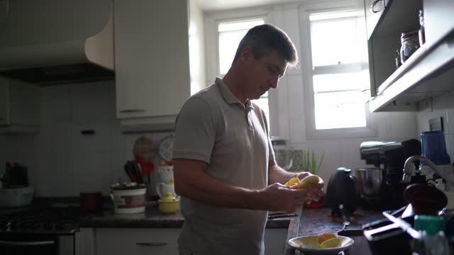 vídeos de stock, filmes e b-roll de homem maduro em casa descascando uma banana - fazer