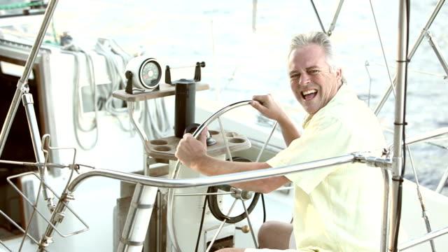 reifer mann an der spitze eines segelbootes - bootskapitän stock-videos und b-roll-filmmaterial
