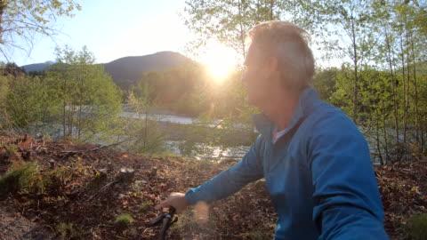 vídeos y material grabado en eventos de stock de mature man bikes along forest trail, sunrise - actividad de fin de semana