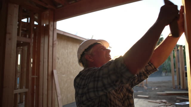 cu mature man building a house at sunset - bauarbeiter stock-videos und b-roll-filmmaterial