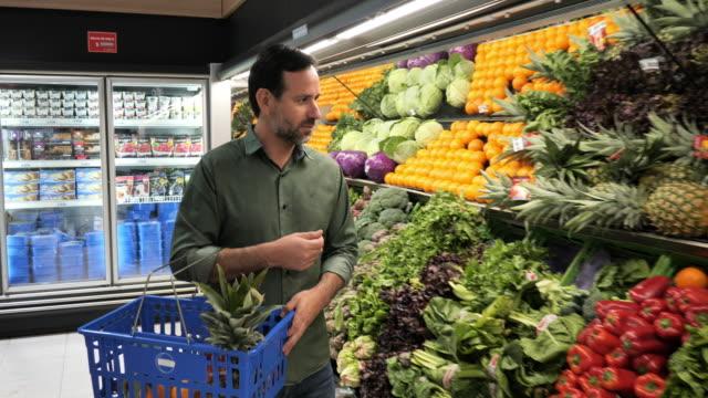 mature man buying fruit in supermarket - organic stock videos & royalty-free footage