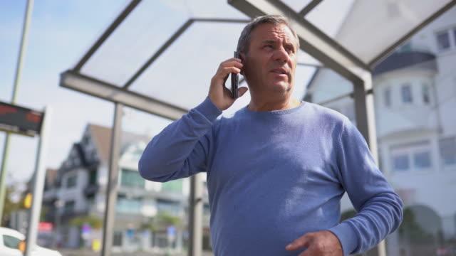 vidéos et rushes de homme mûr appelant un ami en attendant sur la gare routière - regarder autour de soi