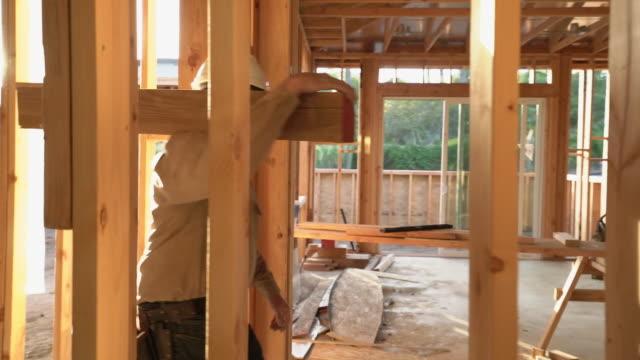vidéos et rushes de ms ts sm mature man carrying a wooden board through a building site. - poutrelle