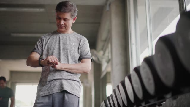 mature man checking pulse by smartwatch at fitness gym. - wearable computer stock videos & royalty-free footage