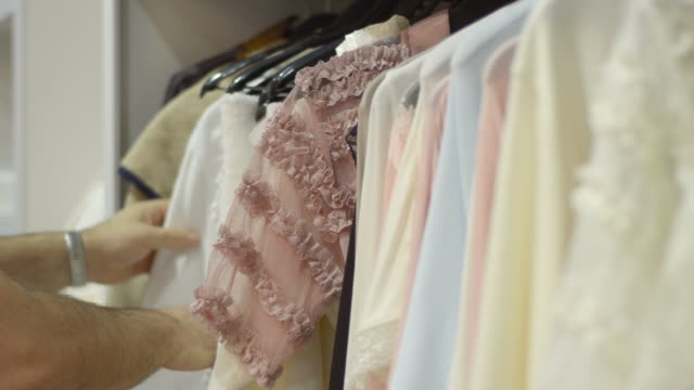 stockvideo's en b-roll-footage met mature man chooses for female new clothes at the mall. - designerkleding