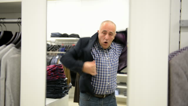 mature man chooses for himself new clothes at the mall. - in front of stock videos & royalty-free footage