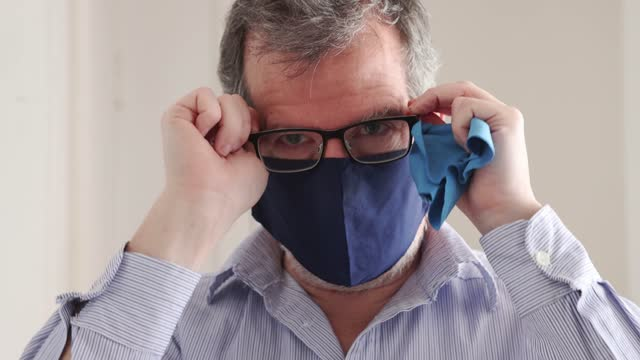 mature man cleaning his eye glasses and adjusting his mask as he leaves home for work - condensation stock videos & royalty-free footage