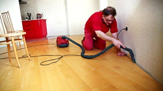 Mature man cleaning the floor with the vacuum cleaner